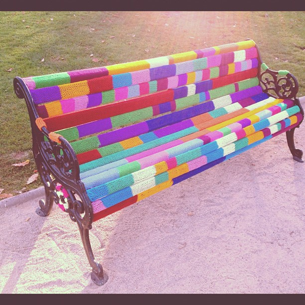 park bench that is covered in knitting